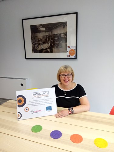Keyworker Beverley sitting at a table with Work. Live. Leicestershire promotional materials.