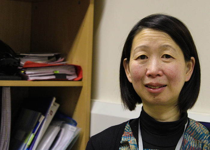 Ling sitting next to a bookcase at Voluntary Action LeicesterShire